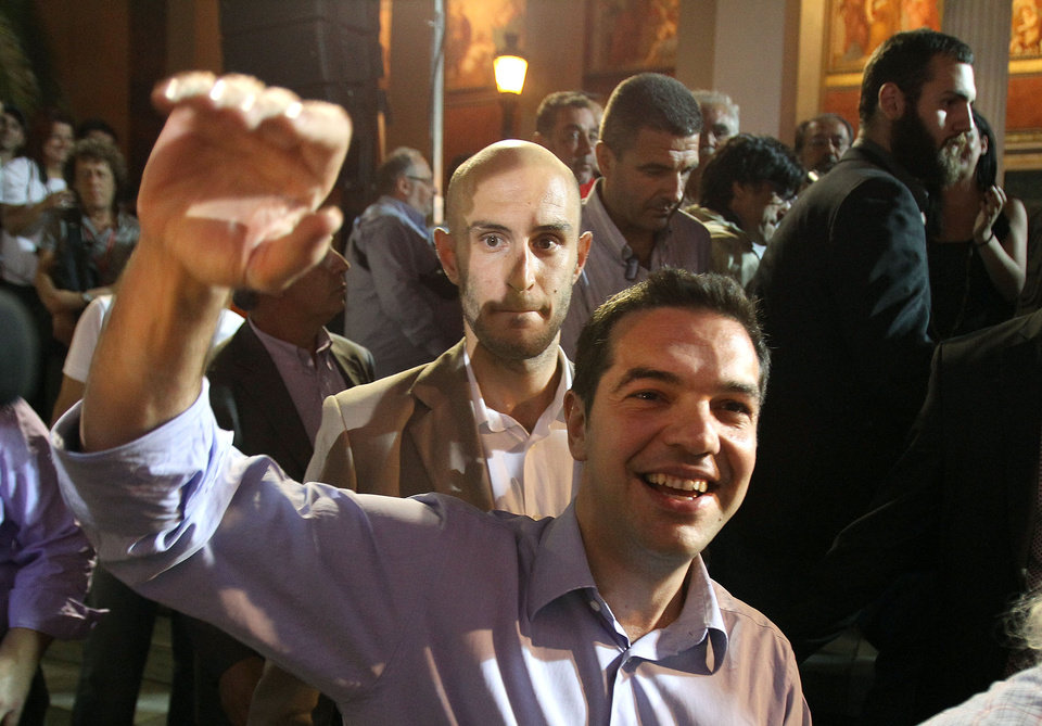 Photo -   Head of Greece's radical left-wing Syriza party Alexis Tsipras waves to his supporters in Athens, late Sunday, June 17, 2012. Alexis Tsipras and his party shot to prominence in the May 6 vote, where he came a surprise second and quadrupled his support since the 2009 election. Syriza party has vowed to rip up Greece's bailout agreements and repeal the austerity measures, which have included deep spending cuts on everything from health care to education and infrastructure, as well as tax hikes and reductions of salaries and pensions. (AP Photo/Petros Karadjias)