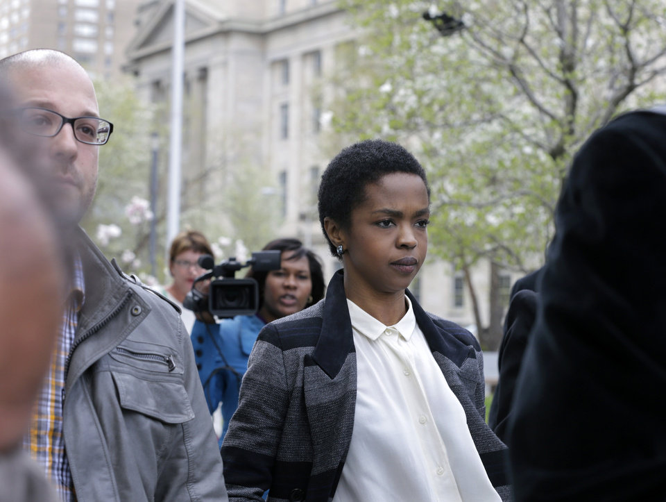 Photo - Singer Lauryn Hill walks from federal court in Newark, N.J., Monday, April 22, 2013, after a judge postponed her  tax evasion sentencing and scolded the eight-time Grammy winner for reneging on a promise to make restitution. Hill pleaded guilty last year to not paying federal taxes on $1.8 million earned from 2005 to 2007. At that time, her attorney said she would pay more than $500,000 by the time of her sentencing. It was revealed Monday in court that Hill has paid $50,000. The South Orange resident got her start with The Fugees and began her solo career in 1998 with the acclaimed album