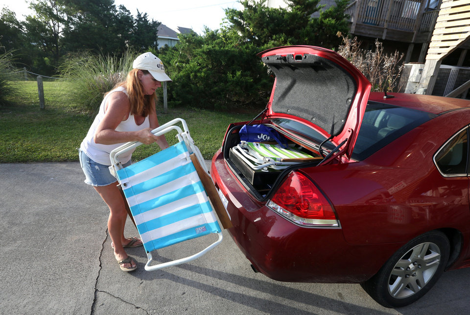 Photo - Carol Palmer of King George, Va.  loads a car with her family's belongings as they prepare to leave Hatteras Village, N.C., on Thursday, July 3, 2014.  Hurricane Arthur is forecast to pass by North Carolina's Hatteras Island Friday morning.  The island is under mandatory evacuation orders.  (AP Photo/The Virginian-Pilot,Steve Earley)   MAGS OUT