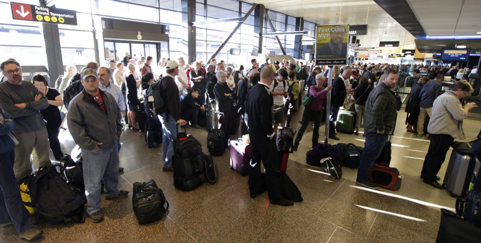 Crowds of Alaska Airlines passengers wait in long lines of the check-in area Monday, Oct. 8, 2012, at Seattle-Tacoma International Airport in Seattle during a system-wide outage of the computers the airline uses to check in passengers. Some flights were able to be checked in manually, but most flights were delayed or canceled. (AP Photo/Ted S. Warren)