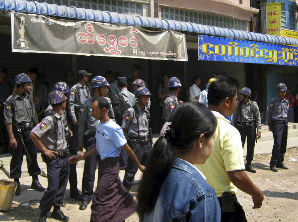 In this Thursday, March. 21, 2013 photo, local people walk past a line of police providing security at a local bazaar following ethnic unrest between Buddhists and Muslims in Meikhtila, Mandalay division, about 550 kilometers (340 miles) north of Yangon, Myanmar. Burning fires from two days of Buddhist-Muslim violence that killed at least 20 people smoldered across a central Myanmar town Friday as residents cowered indoors amid growing fears the country's latest bout of sectarian bloodshed could spread. The government's struggle to contain the unrest in Meikhtila is proving another major challenge President Thein Sein's reformist administration as it attempts to chart a path to democracy after nearly half a century of military rule that once crushed all dissent. (AP Photo)
