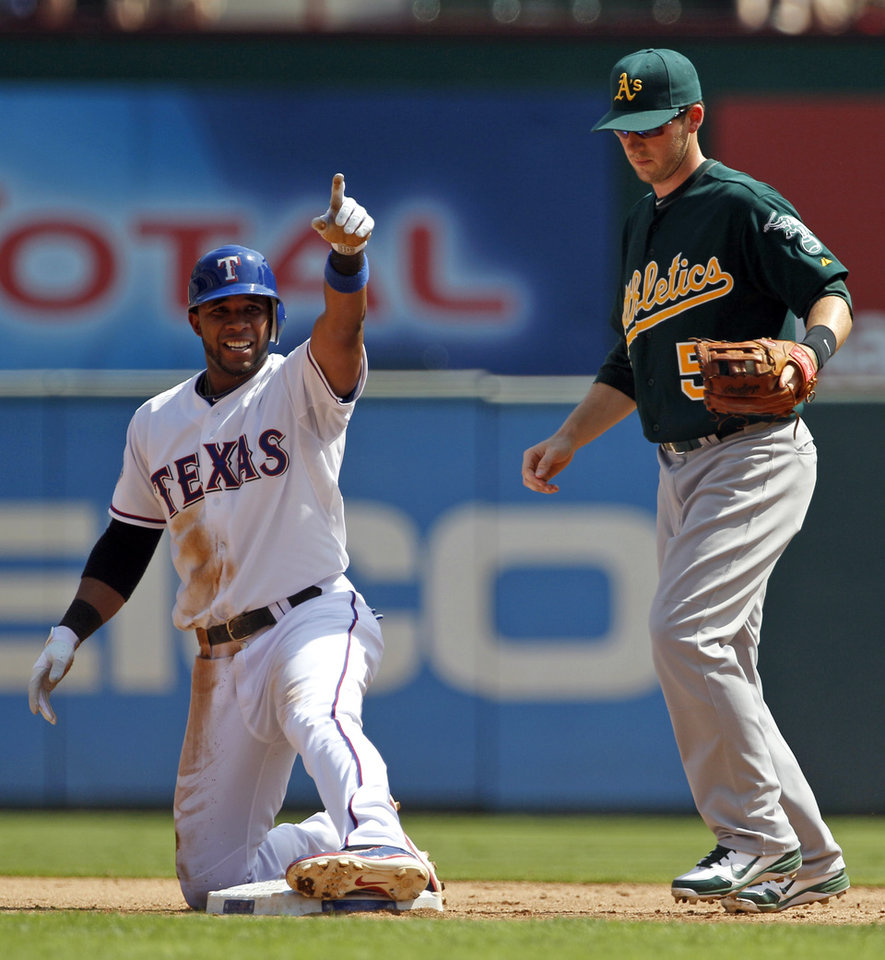 Photo -   Texas Rangers' Elvis Andrus points to the dugout after doubling to right as Oakland Athletics shortstop Stephen Drew (5) watches in the second inning of a baseball game, Thursday, Sept. 27, 2012, in Arlington, Texas. (AP Photo/Tony Gutierrez)