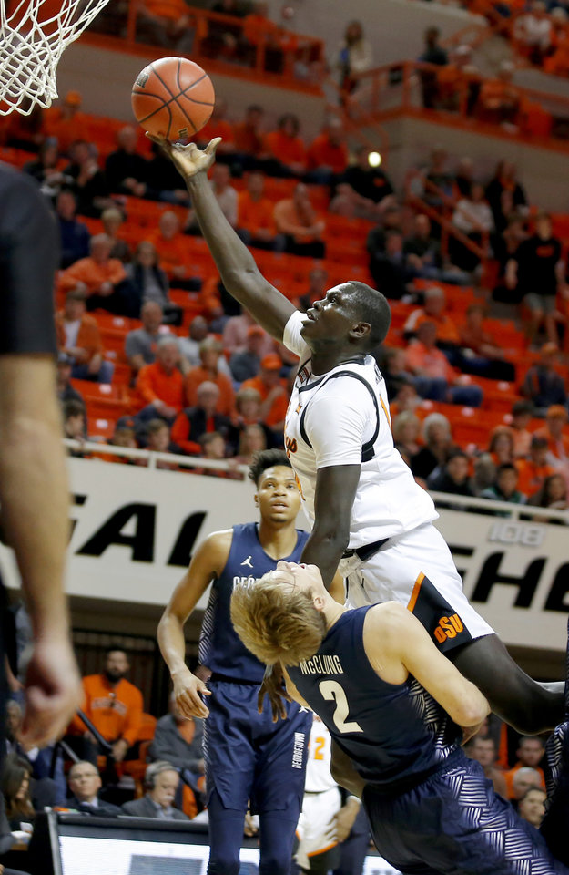 Photo - Oklahoma State's Yor Anei (14) is called for a foul as he collides with Georgetown's Mac McClung (2) during a college basketball game between the Oklahoma State University Cowboys (OSU) and the Georgetown Hoyas at Gallagher-Iba Arena in Stillwater, Okla., Wednesday, Dec. 4, 2019. [Bryan Terry/The Oklahoman]