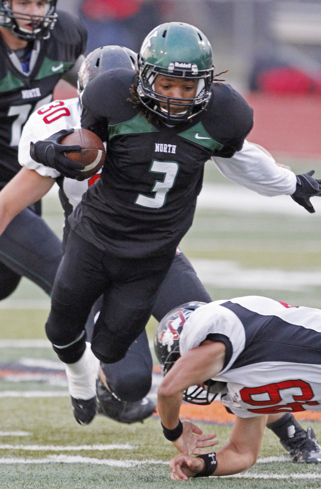 Photo - Norman North's Bryan Payne (3) slips the tackle of Sijon Rider (49) as the Norman North Timberwolves play the Westmoore Jaguars in high school football on Friday, September 16, 2011, in Norman, Okla.   Photo by Steve Sisney, The Oklahoman