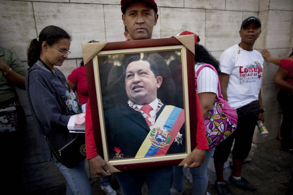 Photo - A supporter of Venezuela's President Hugo Chavez poses for a portrait as he holds a photograph of Chavez outside the National Assembly in Caracas, Venezuela, Saturday, Jan. 5, 2013. Just five days remain until Chavez's scheduled inauguration on Thursday, and government officials are suggesting the swearing-in could be delayed as the president fights a severe respiratory infection after cancer surgery in Cuba. (AP Photo/Ariana Cubillos)