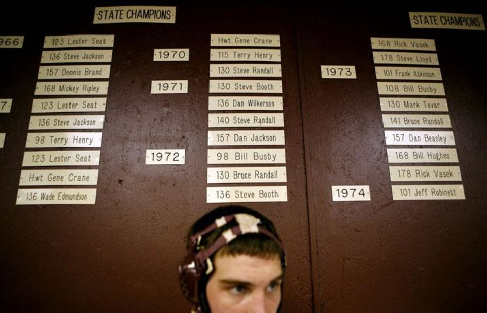 Photo -  Standing under a long list of State Champions from Perry's past, Hayden Workman, a Senior at Perry High School, watches wrestling practice on Wednesday, Feb. 17, 2010. Photo by John Clanton, The Oklahoman