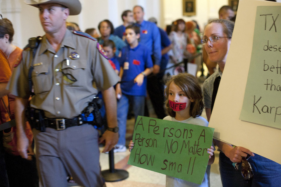 Photo - Linda Maska and Theresa Maska, 8, hold anti-abortion rights signs outside of the Senate Gallery in the State Capitol in Austin, Texas on Friday, July 12, 2013. The Texas Senate's leader, Lt. Gov. David Dewhurst, has scheduled a vote for Friday on the same restrictions on when, where and how women may obtain abortions in Texas that failed to become law after a Democratic filibuster and raucous protesters were able to run out the clock on an earlier special session. (AP Photo/Tamir Kalifa)