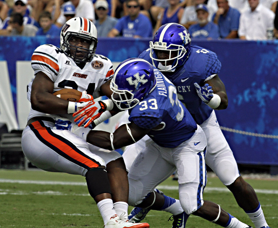 Photo - Kentucky defenders Ryan Flannigan (33) and Jason Hatcher (6) stop Tennessee-Martin running back Abou Toure (24) for a loss in the first half of an NCAA college football game in Lexington, Ky., Saturday, Aug. 30, 2014. (AP Photo/Garry Jones)