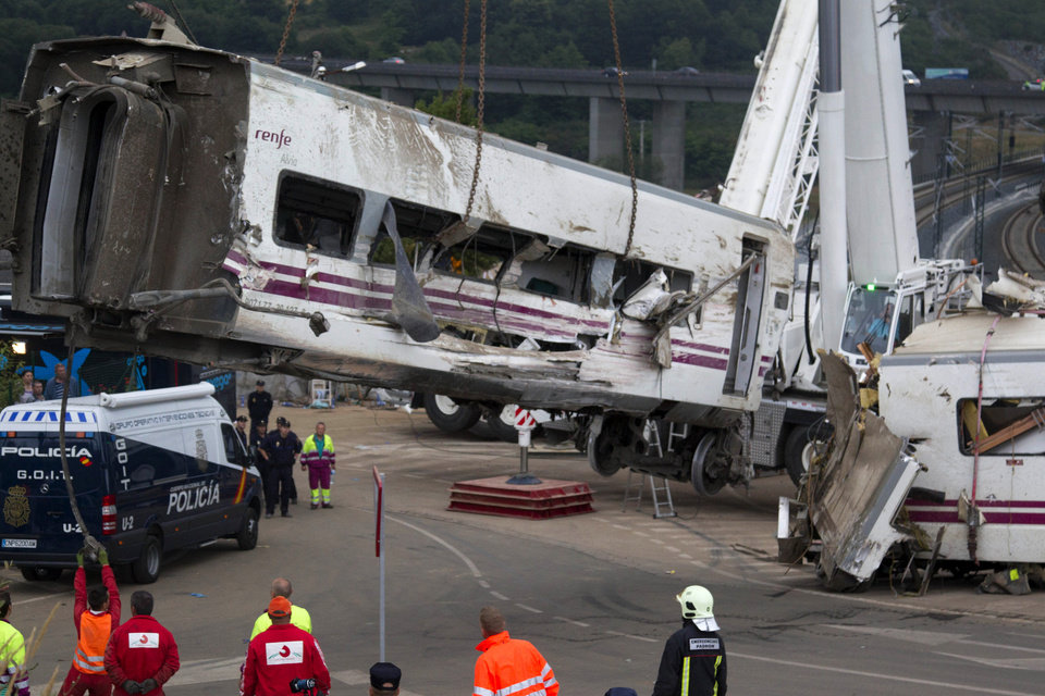 Photo - Derailed cars are removed as emergency personnel work at the site of a train accident in Santiago de Compostela, Spain on Thursday July 25, 2013. The death toll in a passenger train crash in northwestern Spain rose to more than 70 on Thursday after the train jumped the tracks on a curvy stretch just before arriving in the northwestern shrine city of Santiago de Compostela, a judicial official said. (AP Photo/Lalo Villar)