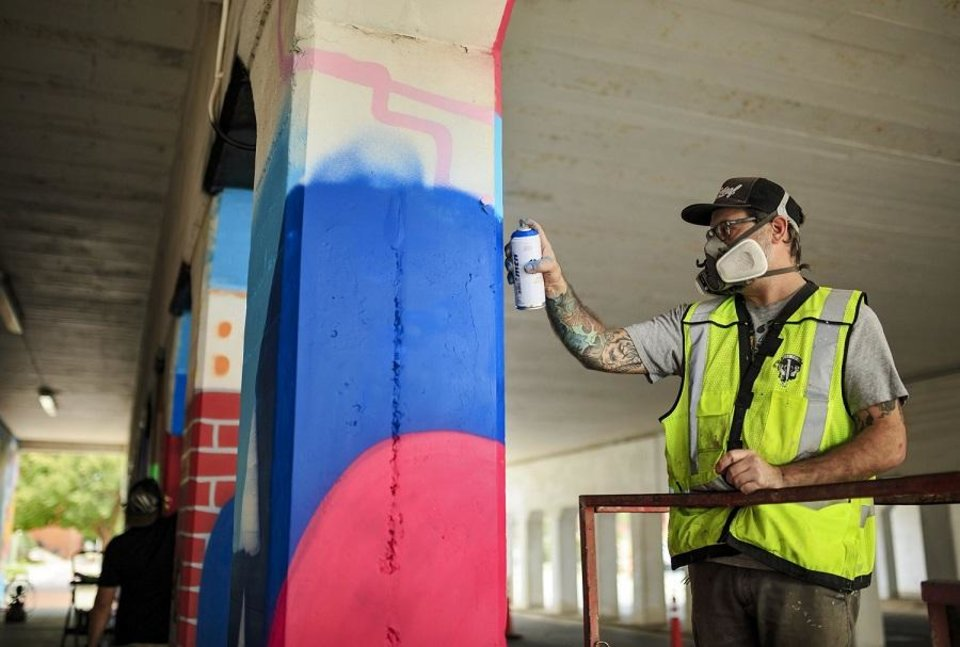 Photo - Artist Kris Kanaly works with spray paint to complete his mural 'Abstract Passages' on the Santa Fe Railroad over Main Street into Bricktown in Oklahoma City, Okla. on Friday, Oct. 20, 2017. [Chris Landsberger/The Oklahoman Archives]