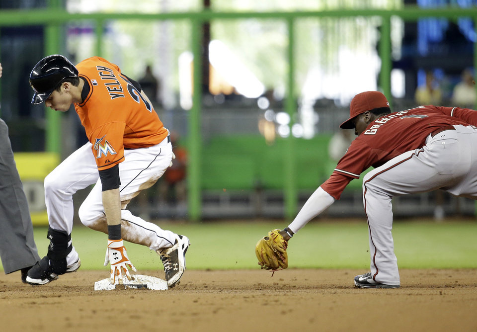 Photo - Miami Marlins' Christian Yelich, left, beats the throw to Arizona Diamondbacks shortstop Didi Gregorius, right, as he is safe with a double in the first inning during a baseball game, Sunday, Aug. 17, 2014, in Miami. (AP Photo/Lynne Sladky)