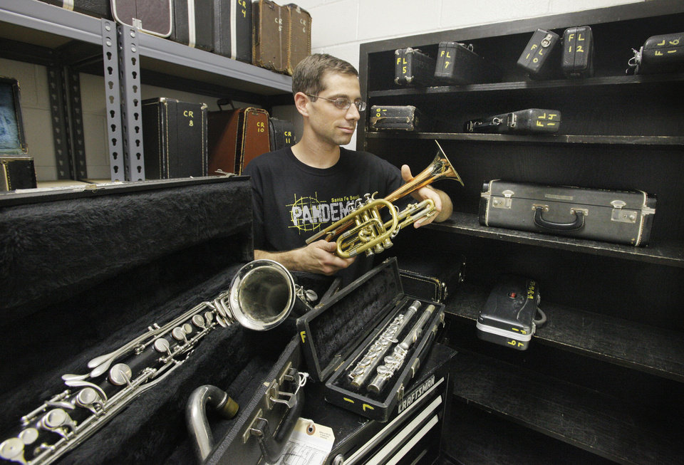 Photo - Band director Scott Filleman sorts through instruments in need of repair work that are used in the band program at Santa Fe South Schools in Oklahoma. The program still needs about 25 more instruments to meet high enrollment.  PAUL B. SOUTHERLAND - THE OKLAHOMAN