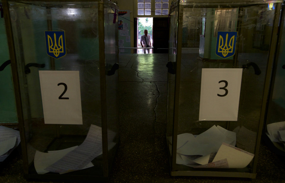 Photo - A local resident arrives to a polling station in Mariupol, Ukraine, on Sunday, May 25, 2014. Ukraine's critical presidential election got underway Sunday under the wary scrutiny of a world eager for stability in a country rocked by a deadly uprising in the east. (AP Photo/Ivan Sekretarev)