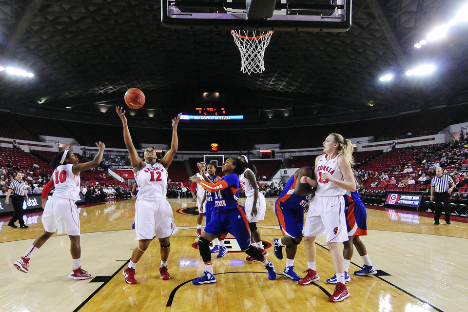 Photo -   Georgia's Jasmine Hassell (12) reaches for a rebound as Savannah State forward Erin Hogue (14) watches during the first half of an NCAA college basketball game in Athens, Ga., Tuesday, Nov. 20, 2012. (AP Photo/AJ Reynolds)