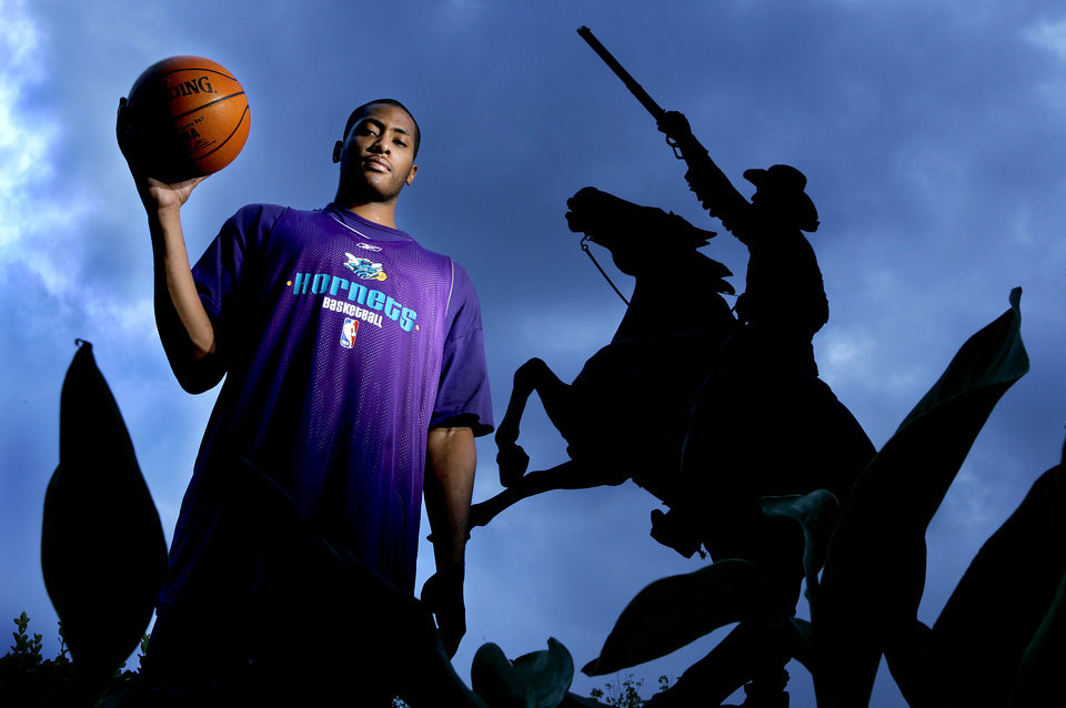 Photo - NBA BASKETBALL:   Jamaal Magloire of the New Orleans/Oklahoma CIty Hornets by the Buffalo Bill statue at the National Cowboy & Western Heritage Museum in Oklahoma, October 11, 2005, in Oklahoma City, Okla.  By Bryan Terry/The Oklahoman