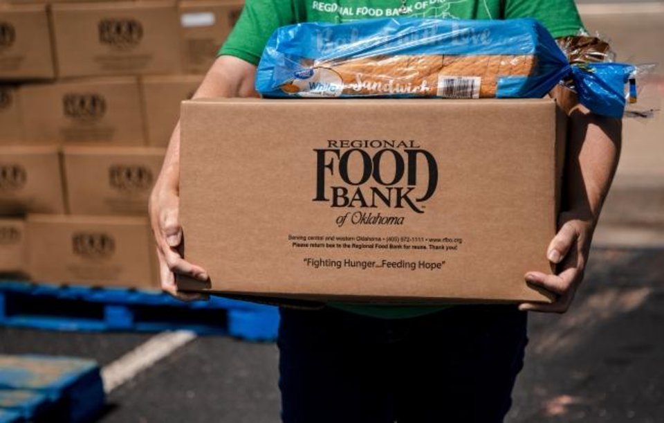 Photo -  Katelyn Gleason-Dockery prepares to load a box of food into a clients car during the Regional Food Bank of Oklahoma food distribution event for individuals seeking unemployment assistance on Wednesday, July 8, 2020, in Midwest City, Okla.  [Chris Landsberger/The Oklahoman]
