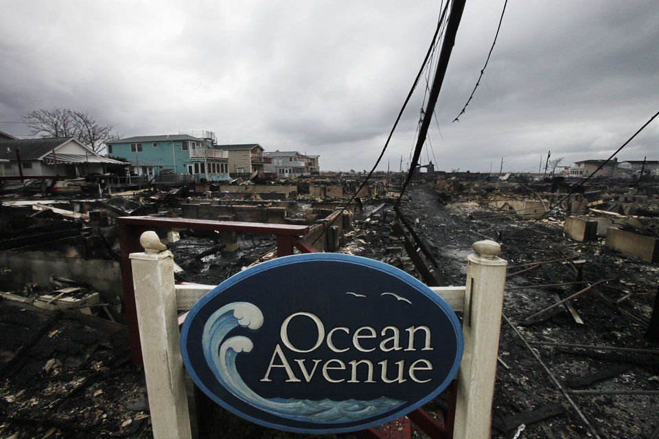 A sign for Ocean Avenue stands in the smoldering ruins of houses in the Breezy Point section of New York, Tuesday, Oct. 30, 2012. More than 50 homes were destroyed in a fire which swept through the oceanfront  community during superstorm Sandy. (AP Photo/Mark Lennihan) ORG XMIT: NYML112