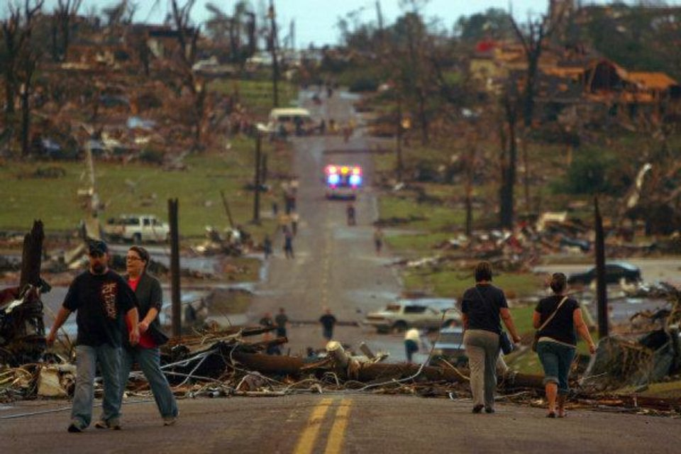 Photo - People walk down a street lined with destroyed homes in Joplin, Mo., Sunday, May 22, 2011. A large tornado moved through much of the city, damaging a hospital and hundreds of homes and businesses. (AP Photo/Mark Schiefelbein) ORG XMIT: MOMS101