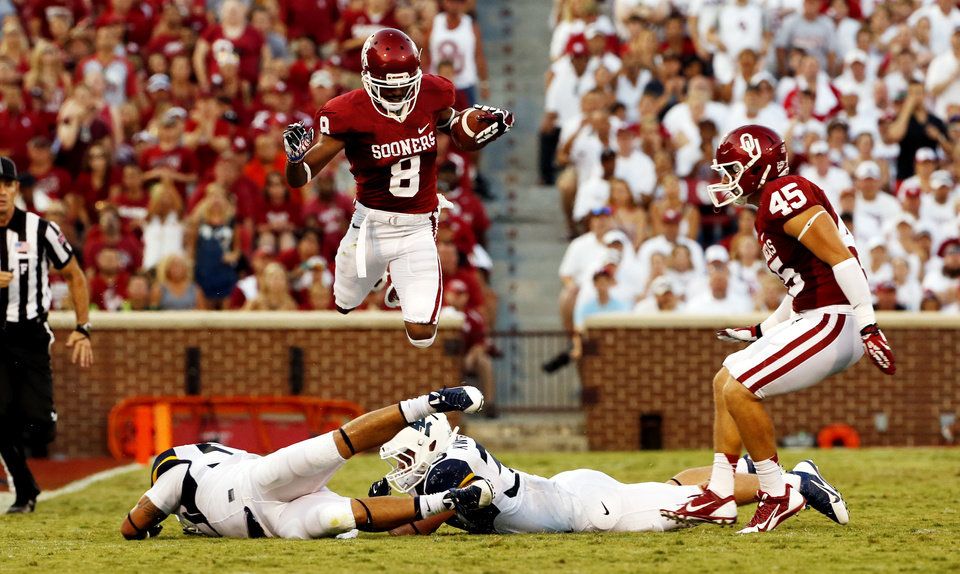 Oklahoma's Jalen Saunders (8) leaps over tacklers on a punt return during a college football game between the University of Oklahoma Sooners (OU) and the West Virginia University Mountaineers at Gaylord Family-Oklahoma Memorial Stadium in Norman, Okla., on Saturday, Sept. 7, 2013. Photo by Steve Sisney, The Oklahoman