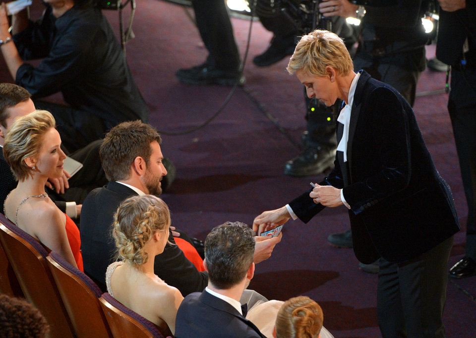 Photo - Ellen DeGeneres, right, gives Bradley Cooper a lottery ticket during the Oscars at the Dolby Theatre on Sunday, March 2, 2014, in Los Angeles.  (Photo by John Shearer/Invision/AP)
