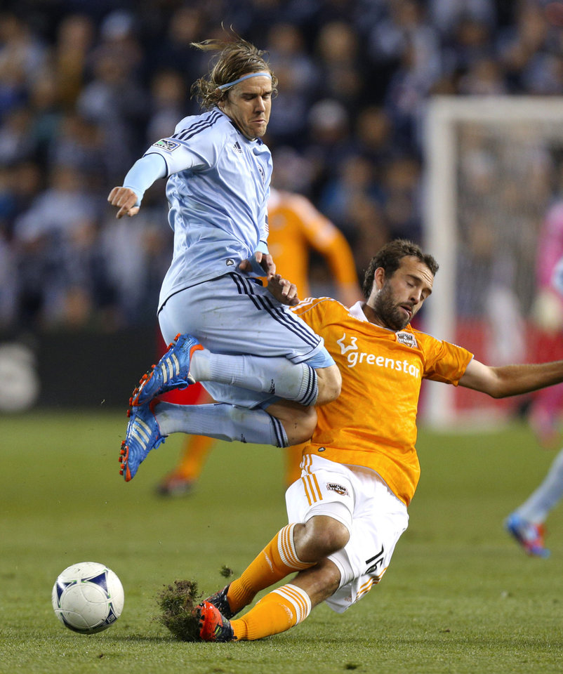 Photo -   Houston Dynamo's Adam Moffat (16) knocks the ball away away from Sporting Kansas City's Chance Myers (7) during the first half of an MLS soccer playoff game Wednesday, Nov. 7, 2012, in Kansas City, Kan. (AP Photo/Ed Zurga)