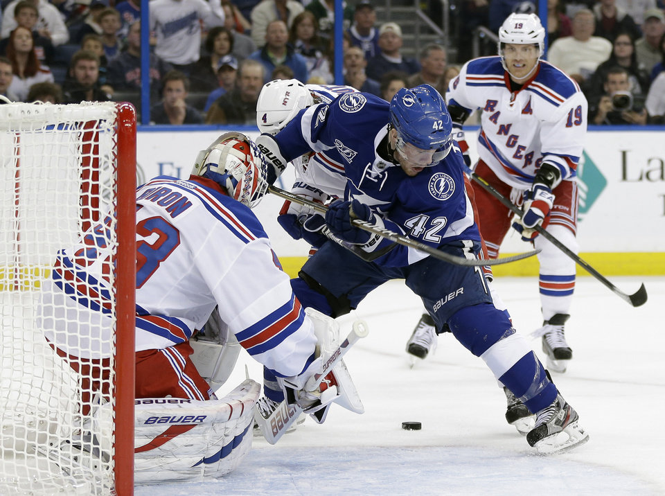 Tampa Bay Lightning center Dana Tyrell (42) loses control of the puck in front of  New York Rangers goalie Martin Biron (43) during the second period of an NHL hockey game on Saturday, Feb. 2, 2013, in Tampa, Fla.  Rangers' Brad Richards, right, trails the play. (AP Photo/Chris O'Meara)