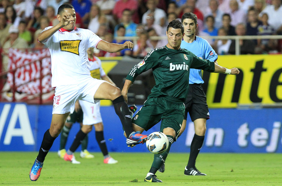 Photo -   Real Madrid's Cristiano Ronaldo from Portugal, right, and Sevilla's Hedwiges Maduro, left, fight for the ball during their La Liga soccer match at the Ramon Sanchez Pizjuan stadium, in Seville, Spain on Saturday, Sept. 15, 2012. (AP Photo/Angel Fernandez)