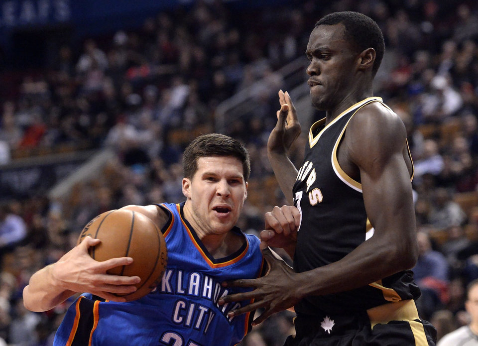 Photo - Oklahoma City Thunder forward Doug McDermott (25) drives to the net past Toronto Raptors forward Pascal Siakam (43) during the second half of an NBA basketball game Thursday, March 16, 2017, in Toronto. (Nathan Denette/The Canadian Press via AP)