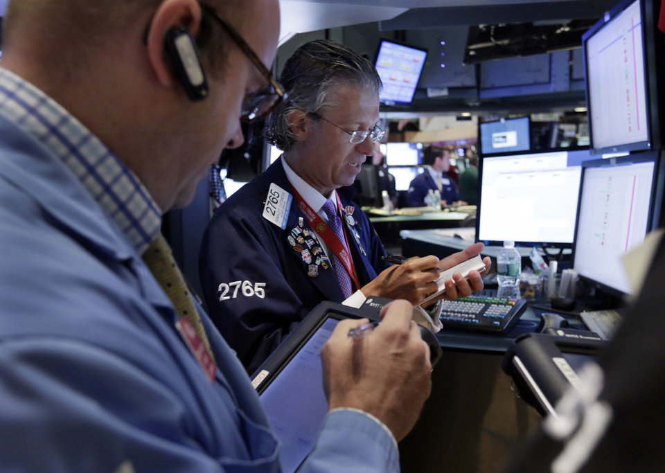 Photo - Specialist Donald Civitanova, center, works with traders on the floor of the New York Stock Exchange Monday, July 22, 2013. The stock market edged higher as a big week of earnings kicked off Monday.   (AP Photo/Richard Drew)
