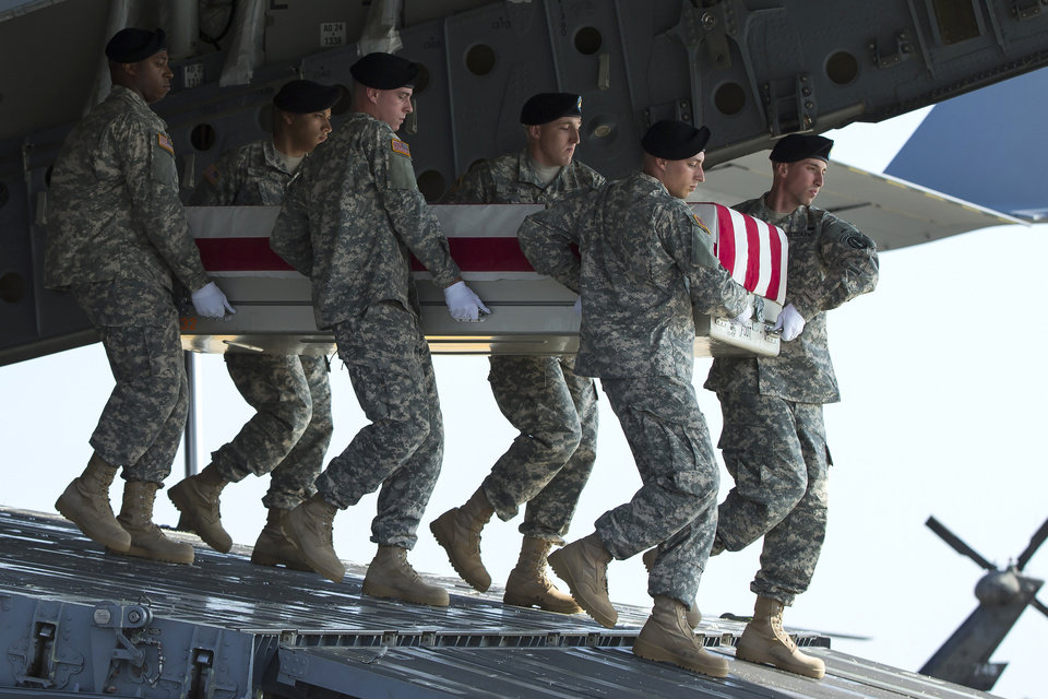 Photo - An Army carry team transfers the remains of Army Maj. Gen. Harold Greene, Thursday, Aug. 7, 2014, at Dover Air Force Base, Del.The C-17 cargo plane carrying the body of Harold Greene landed Thursday morning at Dover, home to the nation's largest military mortuary. Greene is the highest-ranked U.S. officer to be killed in combat since 1970 during the Vietnam War. Greene, a 34-year U.S. Army veteran, also is the highest-ranked American officer killed in combat in the wars in Afghanistan and Iraq.  (AP Photo/Evan Vucci)
