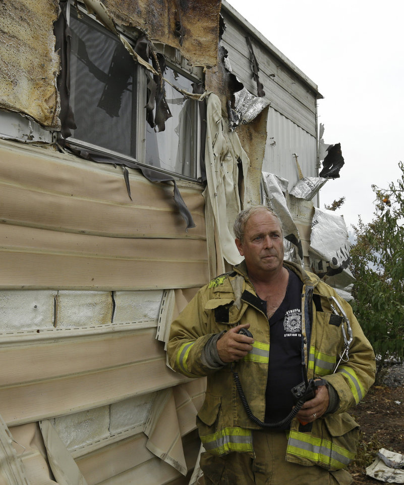 Photo - A Napa firefighter inspects mobile homes that were destroyed Sunday, Aug. 24, 2014, at the Napa Valley Mobile Home Park, in Napa, Calif. A gas fire destroyed four homes at the park after an earthquake struck California's northern San Francisco Bay area early Sunday morning. (AP Photo/Ben Margot)