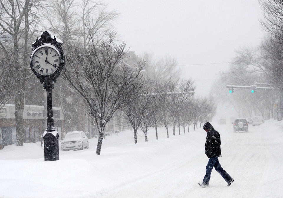 Photo - A pedestrian crosses Main Street as snow falls in downtown Danbury, Conn. Thursday, Feb. 13, 2014.  Danbury and its surrounding areas are expected to see 14 to 20 inches of snow, which is expected to taper off around midnight. (AP Photo/The News-Times, Tyler Sizemore) MANDATORY CREDIT: THE NEWS-TIMES/TYLER SIZEMORE