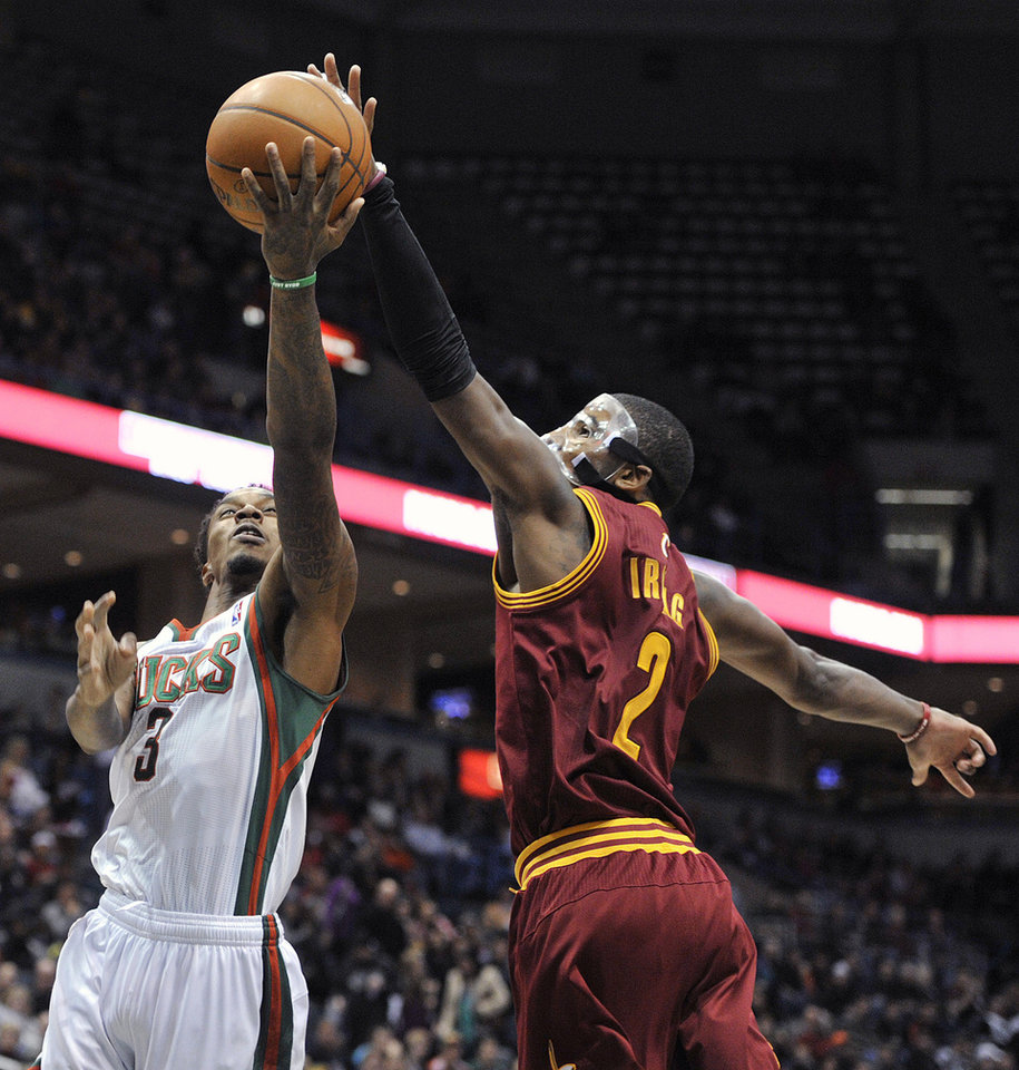 Milwaukee Bucks' Brandon Jennings (3) drives to the basket but has his shot blocked by Cleveland Cavaliers' Kyrie Irving (2) during the second half of an NBA basketball game Saturday, Dec. 22, 2012, in Milwaukee. The Cavaliers defeated the Bucks 94-82. (AP Photo/Jim Prisching)