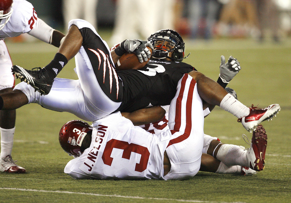 Photo - DJ Woods rolls over Jonathan Nelson (3) and another Sooner and then runs to the end zone thinking he was never tackled during the second half of the college football game between the University of Oklahoma Sooners (OU) and the University of Cincinnati Bearcats (UC) at Paul Brown Stadium on Saturday, Sept. 25, 2010, in Cincinnati, Ohio.  The play was ruled down at this spot.  Photo by Steve Sisney, The Oklahoman