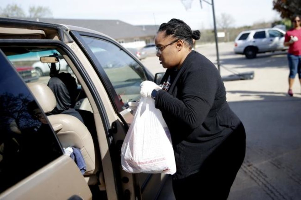 Photo - Jennifer Prince hands a bag food to a family at a drive-thru food distribution for Oklahoma City school students outside The Market at Restore OKC in Oklahoma City, Thursday, March 26, 2020. The drive-thru food distribution was set up on site by Skyline Urban Ministry. [Bryan Terry/The Oklahoman]