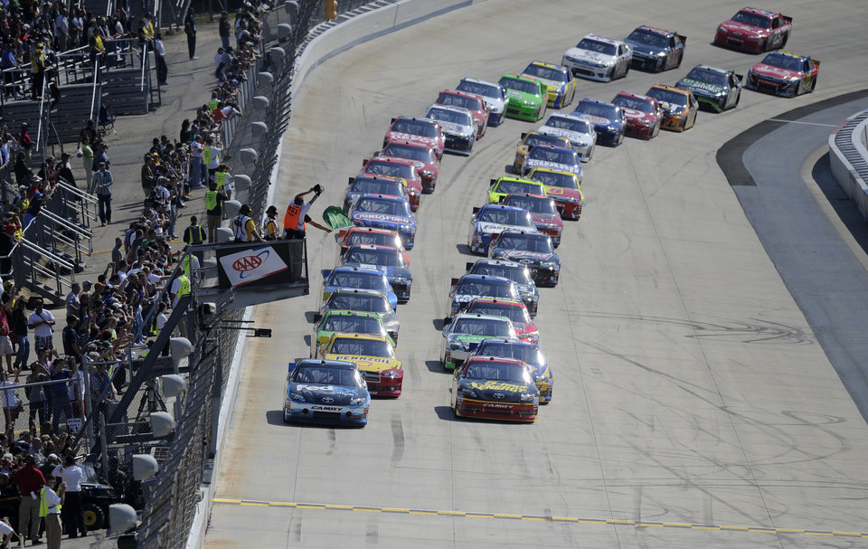 Photo -   Racers take the green flag for the start of a NASCAR Sprint Cup Series auto race, Sunday, Sept. 30, 2012, at Dover International Speedway in Dover, Del. (AP Photo/Nick Wass)