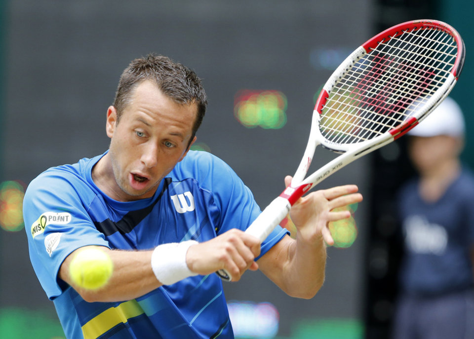 Photo - Germany's Philipp Kohlschreiber hits a backhand against Colombia's Alejandro Falla during the semifinal match of the the Gerry Weber Open tennis tournament in Halle, Germany, Saturday, June 14, 2014. Falla won the match with 5-7, 7-6, 6-4. (AP Photo/Michael Probst)