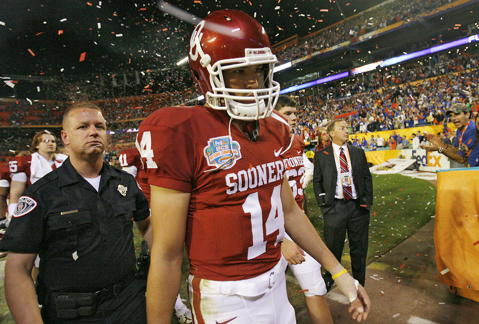 Photo - Oklahoma's Sam Bradford walks off the field after the BCS National Championship college football game between the University of Oklahoma Sooners (OU) and the University of Florida Gators (UF) on Thursday, Jan. 8, 2009, at Dolphin Stadium in Miami Gardens, Fla. Oklahoma lost the game 24-14 to the Gators.