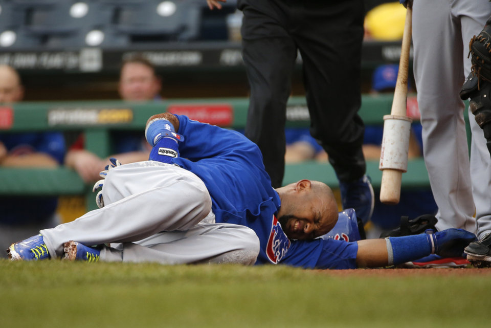 Photo - Chicago Cubs' Emilio Bonifacio lies on the ground after collapsing coming out if the batter's box during the first inning of a baseball game against the Pittsburgh Pirates in Pittsburgh, Thursday, June 12, 2014. Bonifacio was helped to the dugout and left the game. The nature of his injury was not known at the time. (AP Photo/Gene J. Puskar)