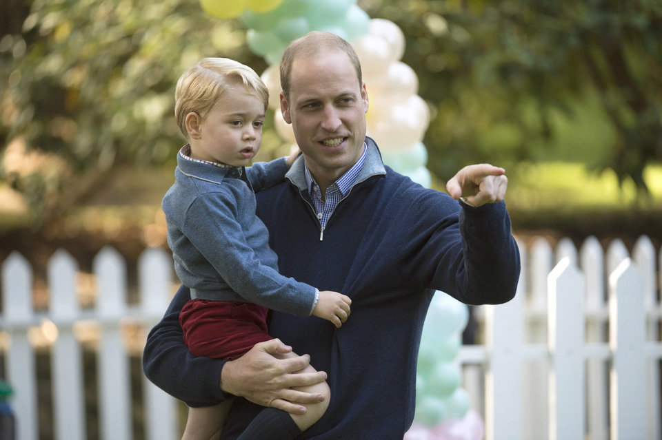 Photo - Prince George holds onto his father Britain's Prince William, the Duke of Cambridge, during a children's party at Government House in Victoria, British Columbia, Thursday, Sept. 29, 2016. (Jonathan Hayward/The Canadian Press via AP)