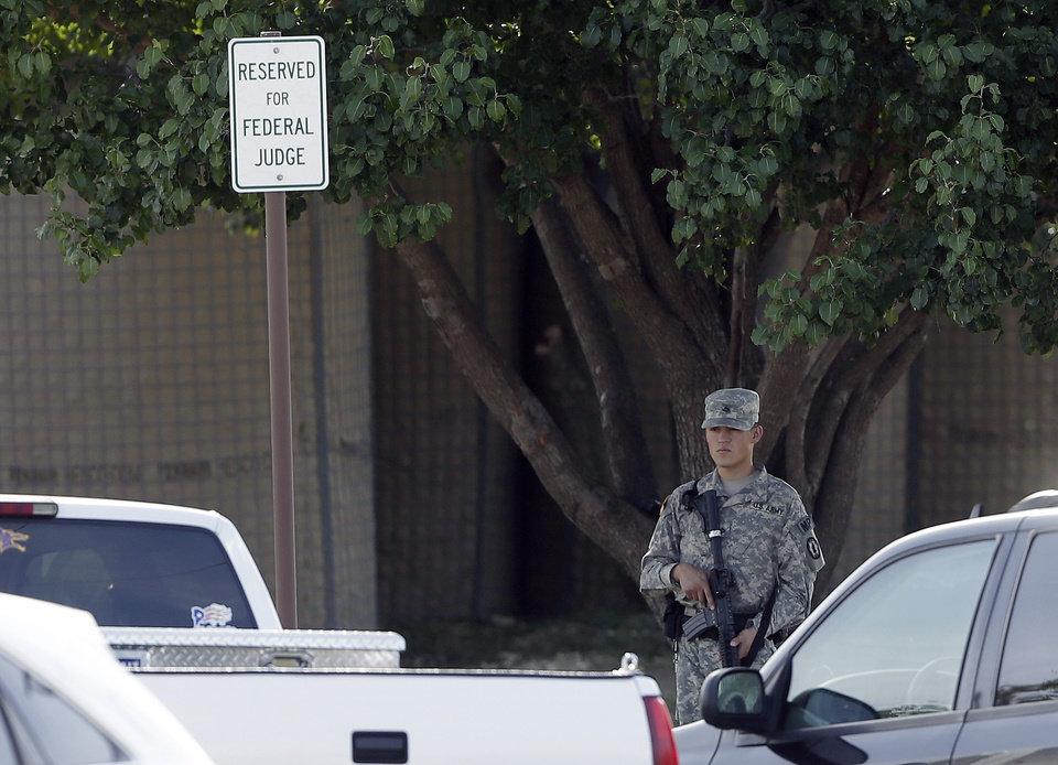 Photo - An armed guard stands in front of the fortified   Lawrence William Judicial Center as the sentencing phase for Maj. Nidal Hasan continues, Wednesday, Aug. 28, 2013, in Fort Hood, Texas. Hasan was found unanimously guilty on the 13 charges of premeditated murder and is eligible for the death penalty. (AP Photo/Eric Gay)