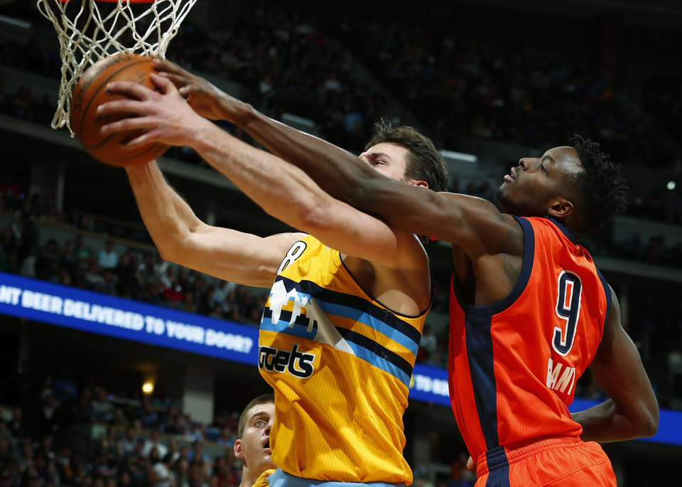 Photo - Denver Nuggets forward Danilo Gallinari (8) and Oklahoma City Thunder forward Jerami Grant (9) go after a rebound during the first half of an NBA basketball game, Sunday, April 9, 2017, in Denver. (AP Photo/Jack Dempsey)
