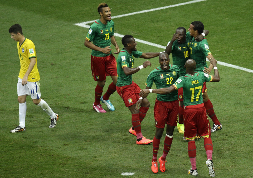 Photo - Cameroon's Joel Matip, right, celebrates with team mates after scoring his side's first goal during the group A World Cup soccer match between Cameroon and Brazil at the Estadio Nacional in Brasilia, Brazil, Monday, June 23, 2014. (AP Photo/Christophe Ena)