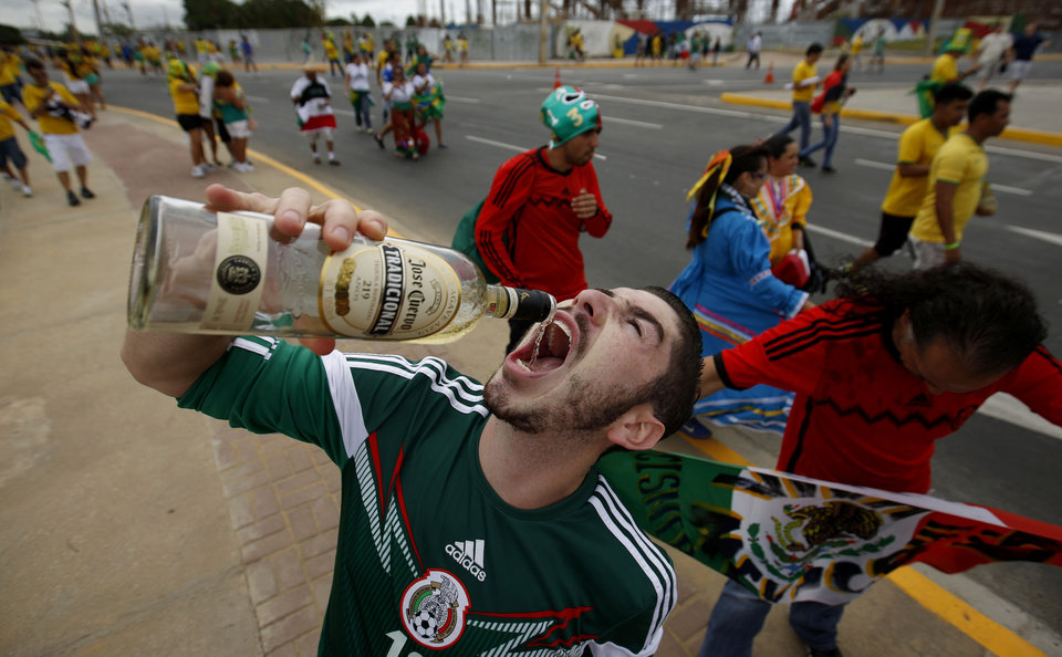 Photo - A Mexican fans drinks tequila outside of the Arena Castelao stadium before the group A World Cup soccer match between Brazil and Mexico in Fortaleza, Brazil, Tuesday, June 17, 2014. Many of the soccer fans traveling from the U.S. to Brazil, are part of the last great wave of Mexican migration to the United States, which spanned the 1990s to the mid-2000s. Others are second-generation Mexicans who grew up rooting for the Mexican team at a time when Team USA was still unknown. (AP Photo/Eduardo Verdugo)