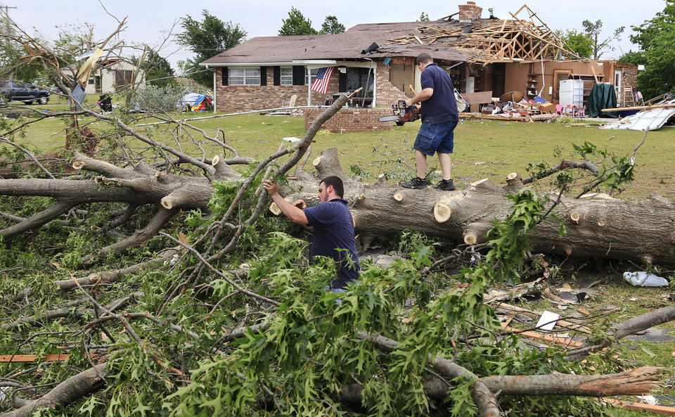 A pair of volunteers from the Pentecostal Church of God in Tecumseh, cut and stack the branches of this large tree that was knocked down by the force of Monday night's tornado that struck the Pottawatomie County community.     Photo by Jim Beckel, The Oklahoman