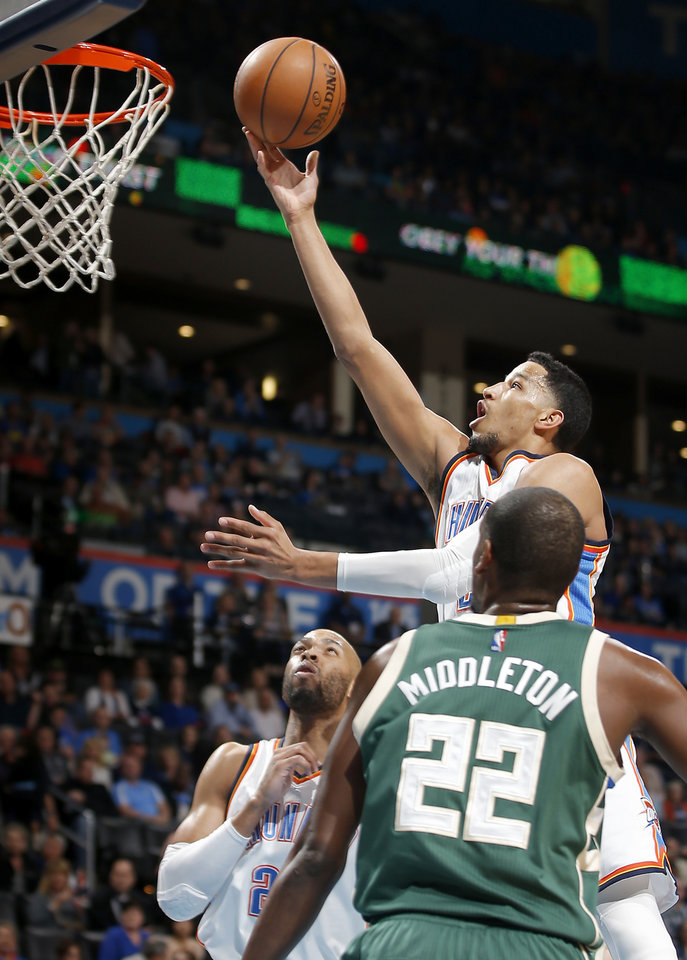 Photo -  Oklahoma City's Andre Roberson goes past Milwaukee's Khris Middleton to the basket Tuesday. [Photo by Bryan Terry, The Oklahoman]