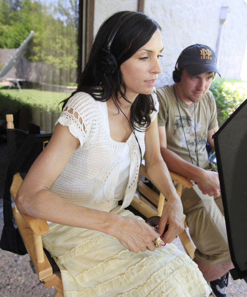 Photo - Actress turned writer-director Famke Janssen watches a monitor during filming of a scene for the movie