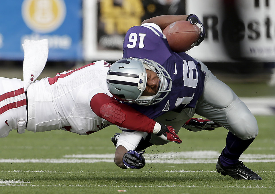 Kansas State wide receiver Tyler Lockett (16) is tackled by Oklahoma linebacker Londell Taylor (31) during the first half of an NCAA college football game Saturday, Nov. 23, 2013 in Manhattan, Kan. (AP Photo/Charlie Riedel)
