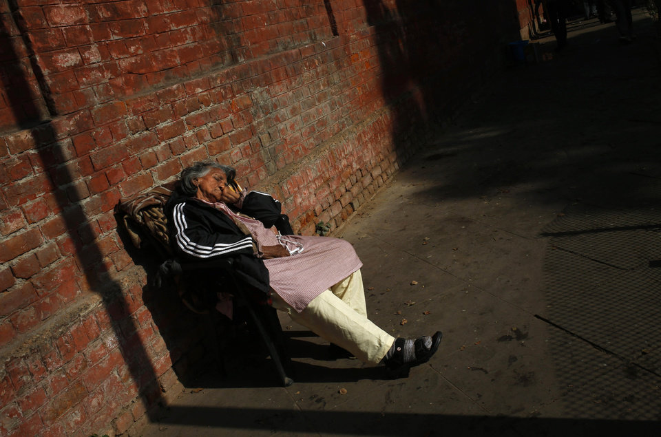 An elderly woman sits the warmth of the sun on a cold winter morning in New Delhi, India, Wednesday, Jan. 9, 2013. North India continues to face below average weather conditions with dense fog affecting flights and trains. More than 100 people have died of exposure as northern India deals with historically cold temperatures. (AP Photo/ Saurabh Das)