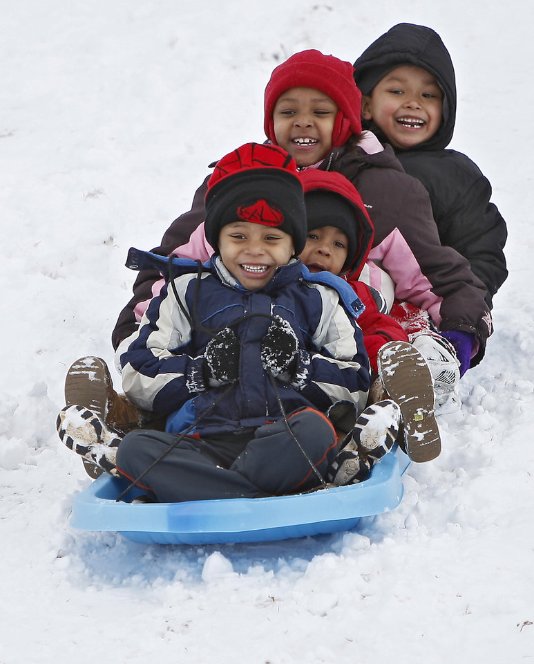 Miguel Howell, 4, in front, Jace Hall, 3, Star Howell, 7, and Melique Miles, 6, sled down a hill at Will Rogers Park in Oklahoma City, Saturday, Jan. 30, 2010.  Photo by Bryan Terry, The Oklahoman